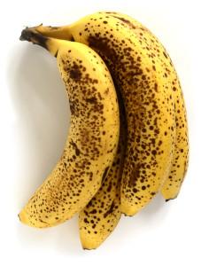 Fire modne bananer der er helt gule og fulde af brune pletter