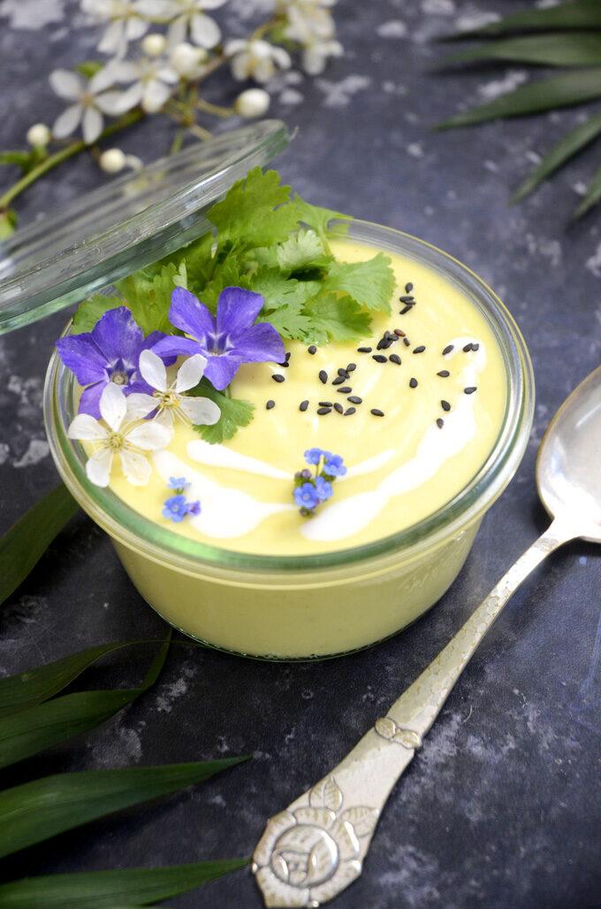 Vegansk blomkåls-thaisuppe pyntet med lilla blomster