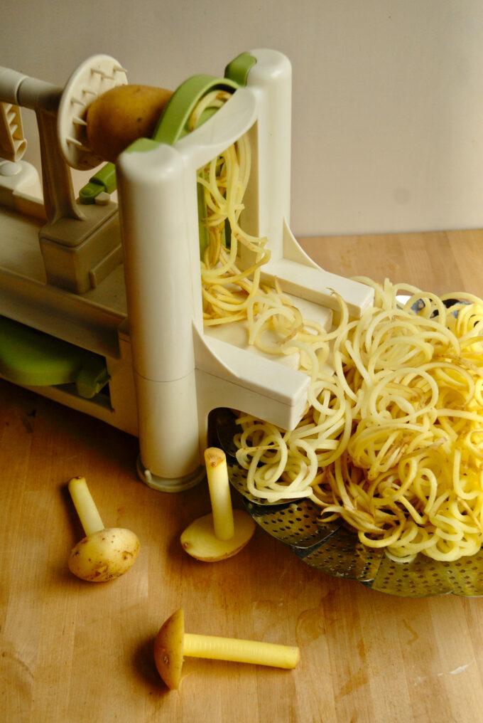 En spiralizer står på en træbord og der ligger en masse strimler kartofler som et blevet lavet af den